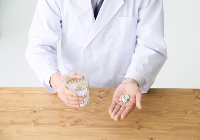 サプリメントを持つ白衣の男性
