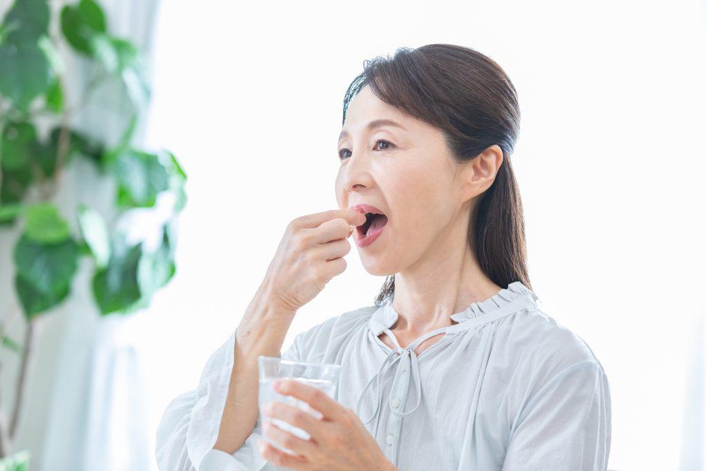 サプリメントを飲む高齢者女性