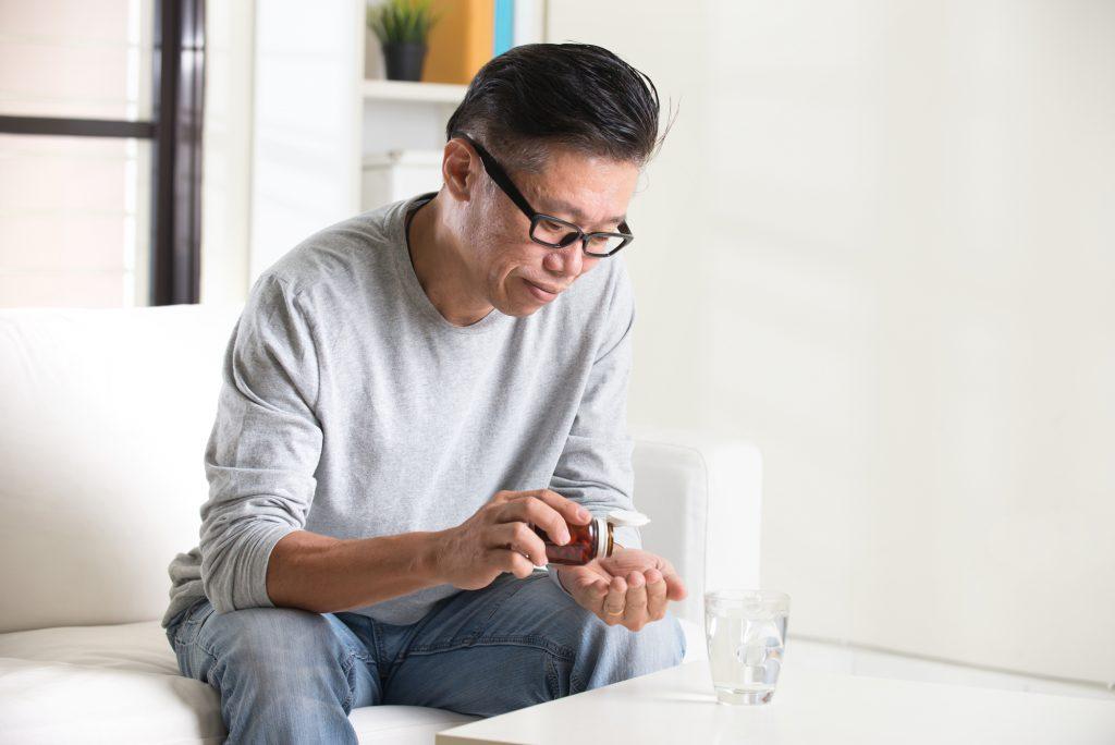 サプリメントを飲む中国人男性
